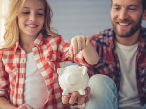 Father and daughter saving in piggy bank